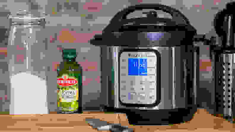 An Instant Pot on a table besides a cutting board a bottle of olive oil and a jar of flour.