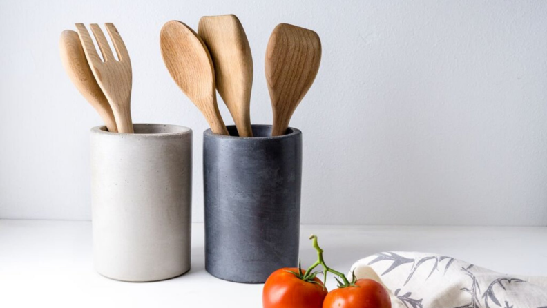 Two utensil holders house spatulas and spoons.