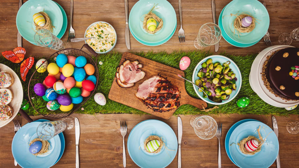 A decorated table for Easter dinner with glazed ham, painted eggs, tulips and Easter cake.