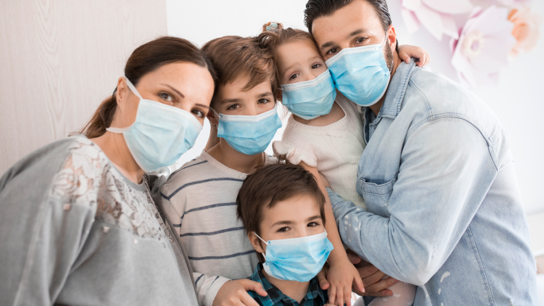 A family of five all wearing face masks