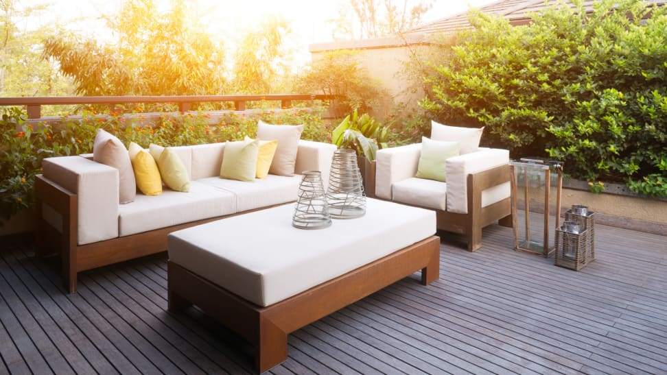 A patio space with a matching outdoor sofa, chair, and coffee table surrounded by green shrubbery