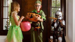 Three kids wearing Halloween costumes: Tinker Bell, Peter Pan, and the Mandalorian