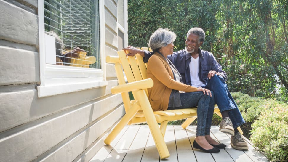 A couple sits on an outside porch.