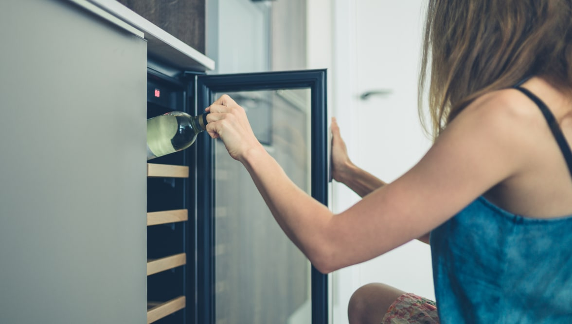 A woman pulls a bottle of wine out of a wine refrigerator.