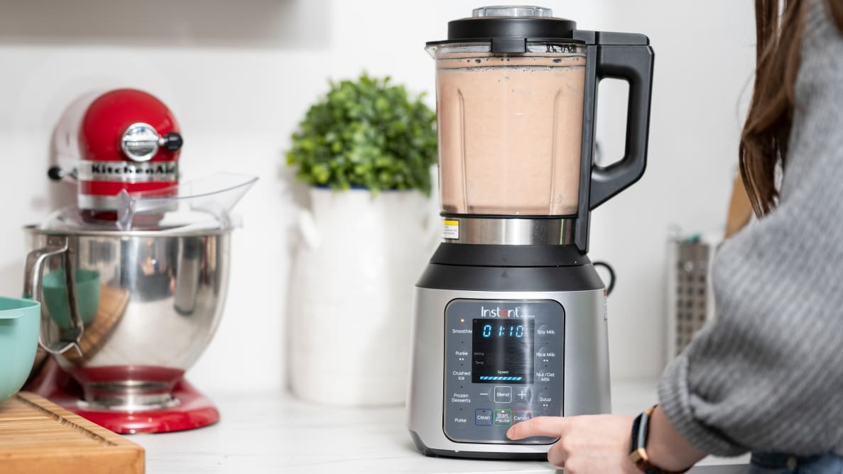 A person blends a smoothie in a blender on a countertop surrounded by other kitchen items.