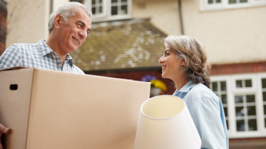 Two people moving into a house stand outside carrying a box and a lamp.