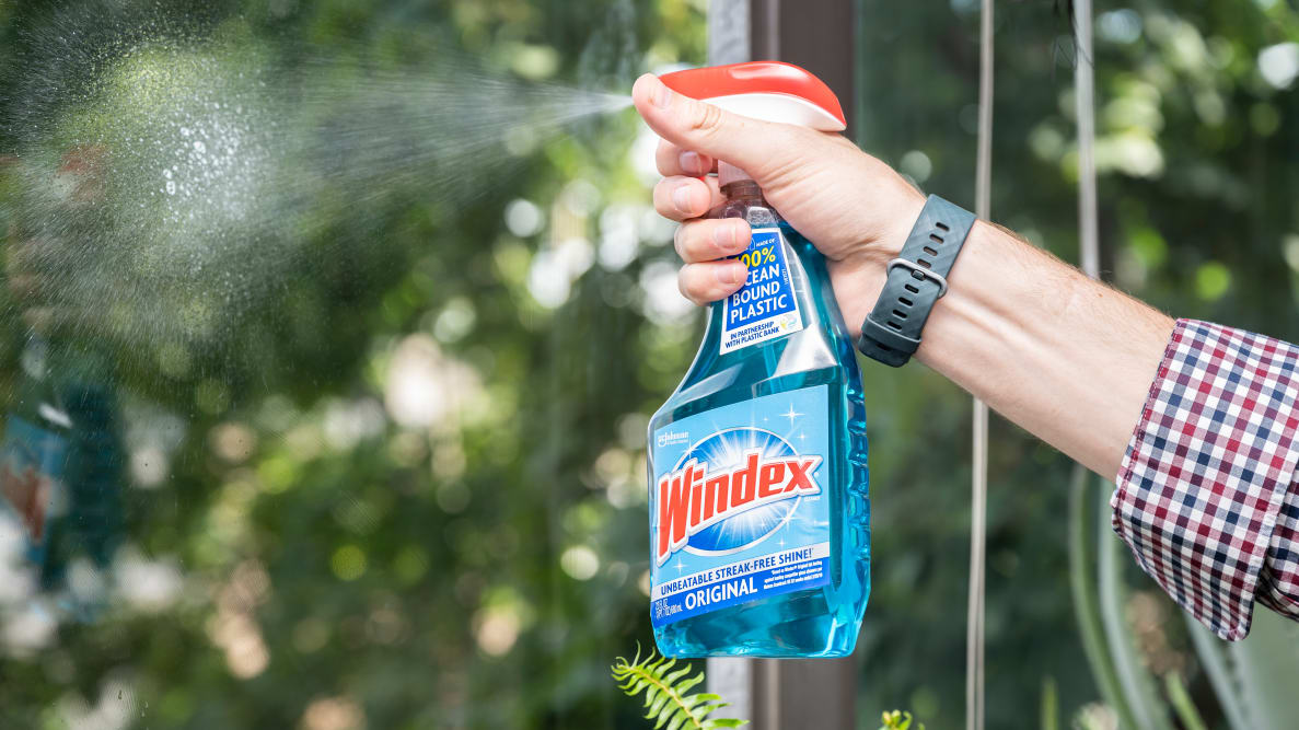 A person sprays a glass cleaner on a clear window with green trees in the background