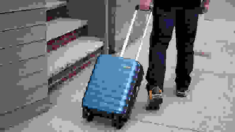 A hardshell carry-on bag is pulled down a sidewalk, by its extendable handle