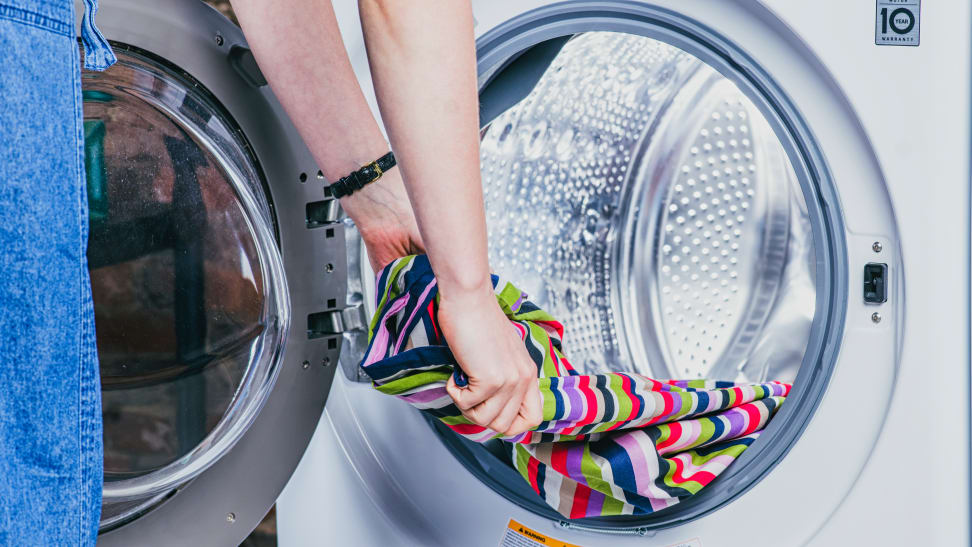 A person removing clothes from a front-load washer.
