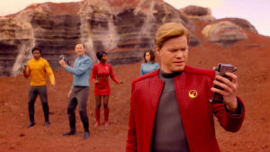 A still from the Star Trek episode of 'Black Mirror,' featuring the cast of the episode in Star Trek themed outfits on a planet of rocks and red dirt.