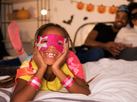 Little girl in costume on a bed