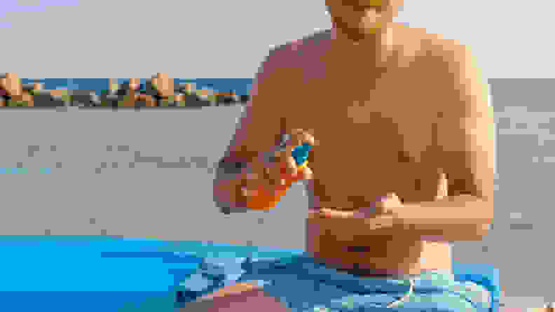 A person sitting on the beach applying sunscreen.