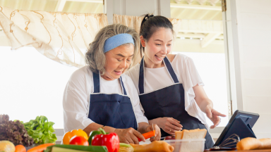 Mother and daughter wearing aprons cooking a meal together