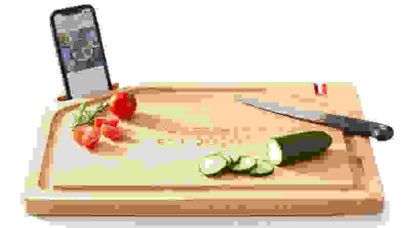 Cutting board with cucumber and tomatoes on it.
