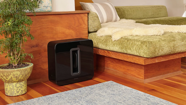 A Sonos Sub sits in a living room.