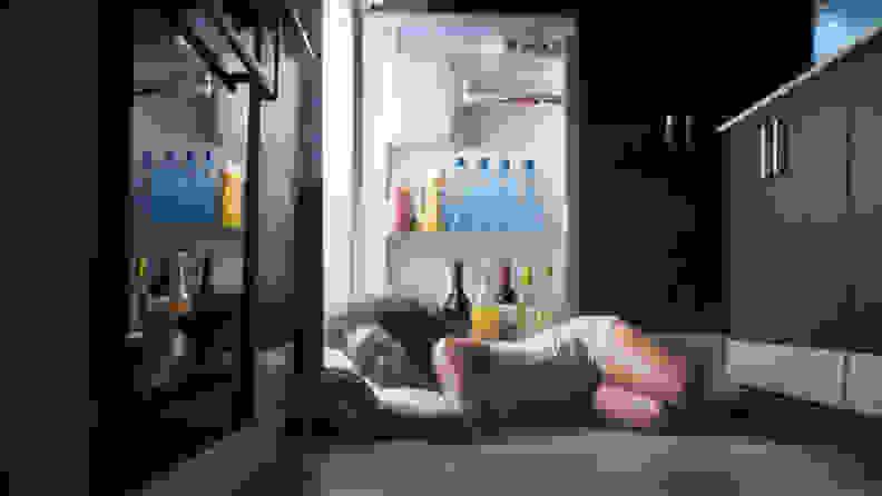 A woman has fallen asleep in front of her open refrigerator door.