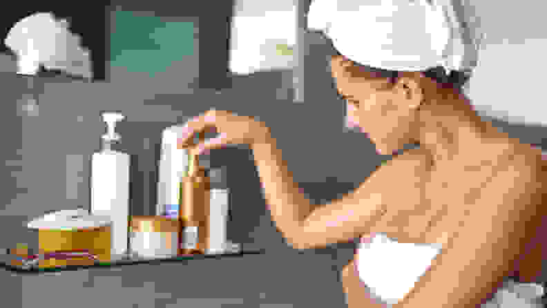 A person wearing a towel around their body and in their hair reaches for a skincare product on a shelf.