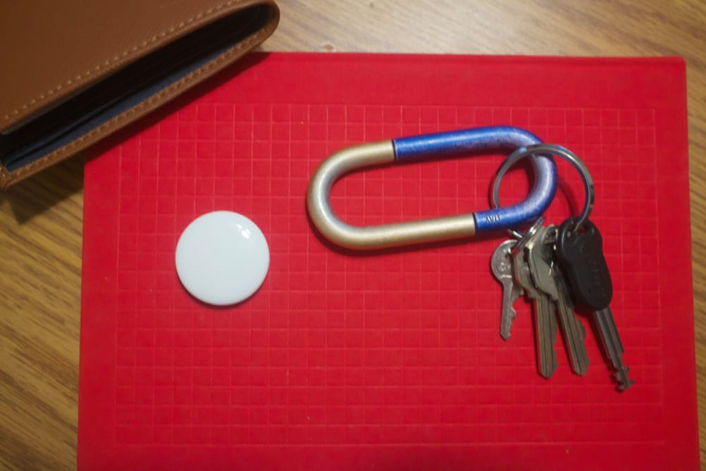 Apple's AirTag tracker, on top of a notebook, next to a wallet and set of keys.