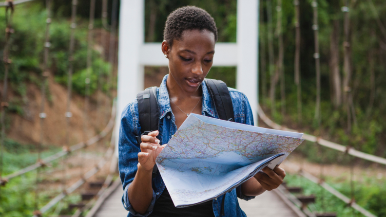 A person walks across a bridge while looking at a trail map.