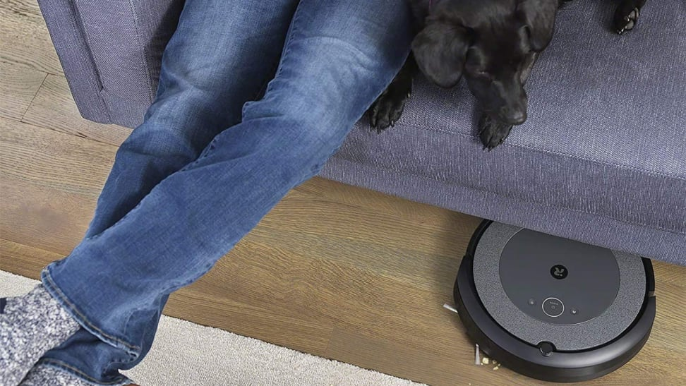 Man on couch with dog. Robot vacuum under couch.
