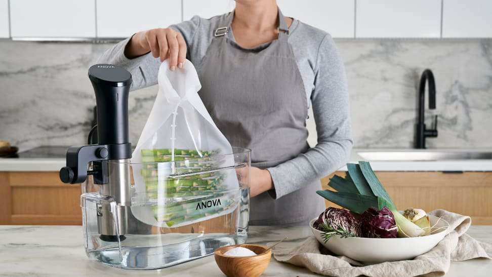 A woman is putting a bag of asparagus into a half-filled water tank for sous vide. An immersion circulator is attached to the tank to control the temperature of the water.