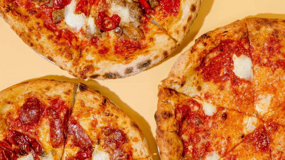 An overhead photo of three wood-fired pizzas, one cheese, one pepperoni, and one sausage and peppers.