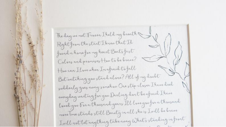 Vows written on cotton page in white frame.
