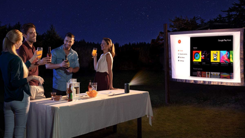 A group of people watch a film outdoor with a mini projector.