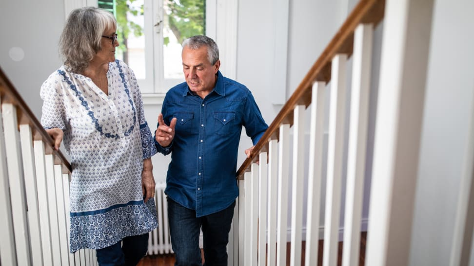 Two senior adults climb the stairs.