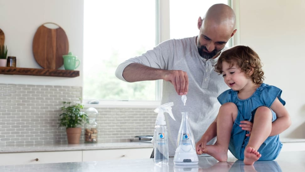 A father shows his young daughter the Force of Nature multi-surface disinfectant.