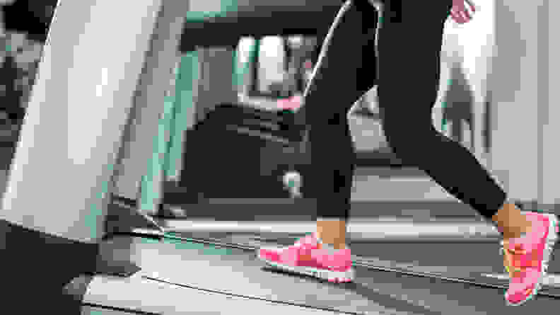 An image of a woman's sneakers while walking uphill on a treadmill.