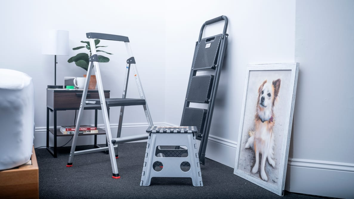 A grouping of three step stools stand in an office next to a portrait of a dog