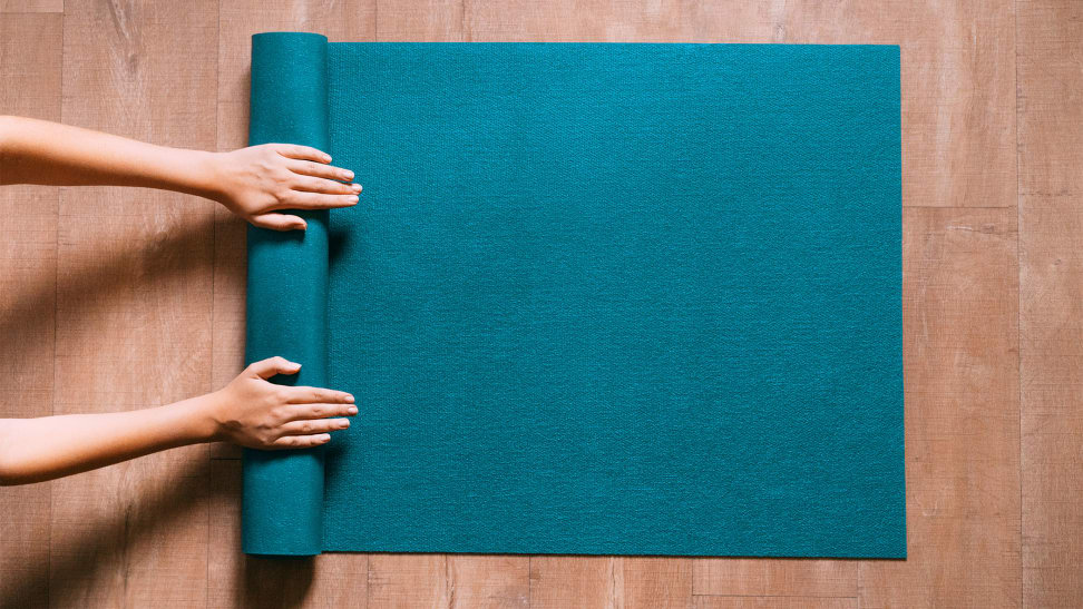 An image of someone rolling up their yoga mat on the floor.