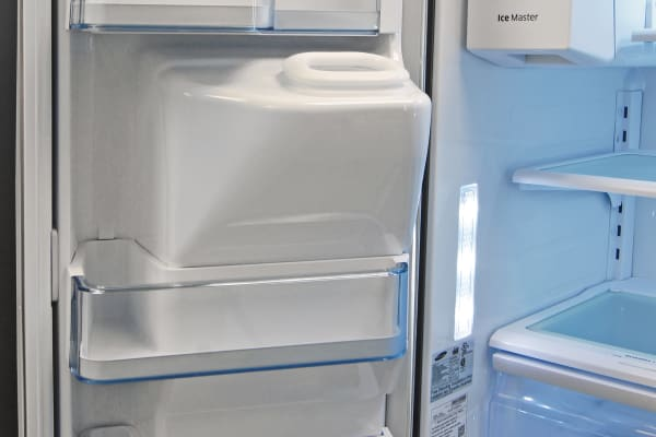 Left-hand door storage is shaped to accommodate the Samsung RF23HTEDBSR's ice dispenser chute.