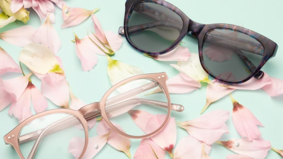 Two pairs of glasses on a green background