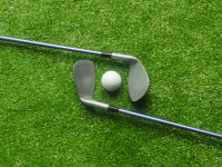 Two golf clubs and a golf ball on a putting green