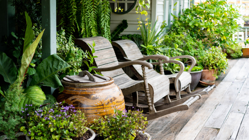 Two wooden rocking chairs on patio surrounded by plants and flowers