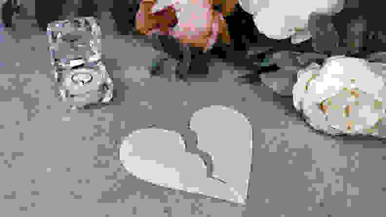 A torn pink heart on table next to box of wedding rings and flowers
