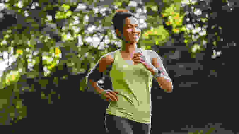 A woman running outdoors listening to music.