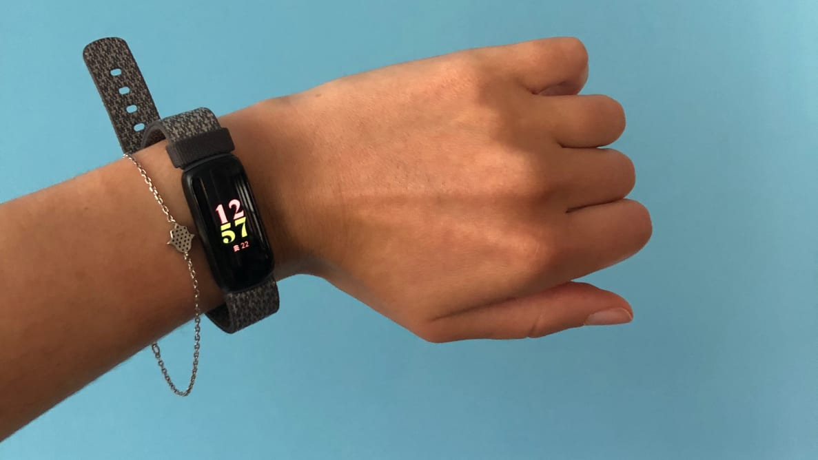 Left: Woman wearing black Fitbit Luxe on blue backdrop. Right: Pink Fitbit Luxe.
