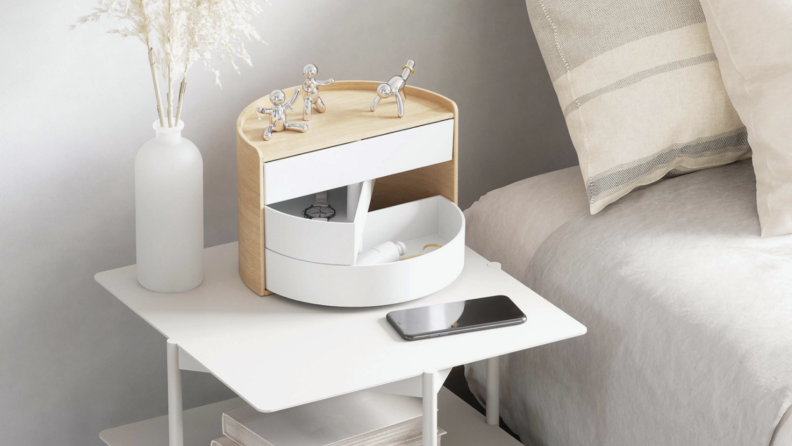 White wooden bedside table organizer from OXO next to bed on nightstand table.