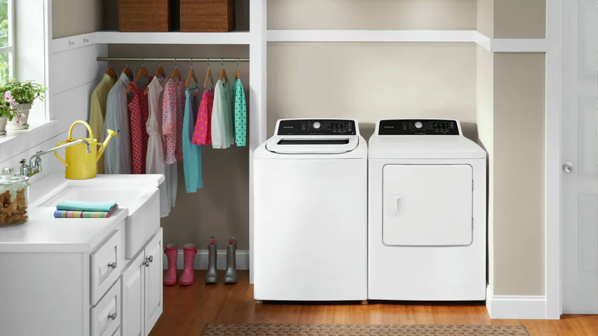 The Frigidaire FFTW4120SW top-load washing machine sits next to its paired dryer, the FFRE4120SW, in a homey laundry room.