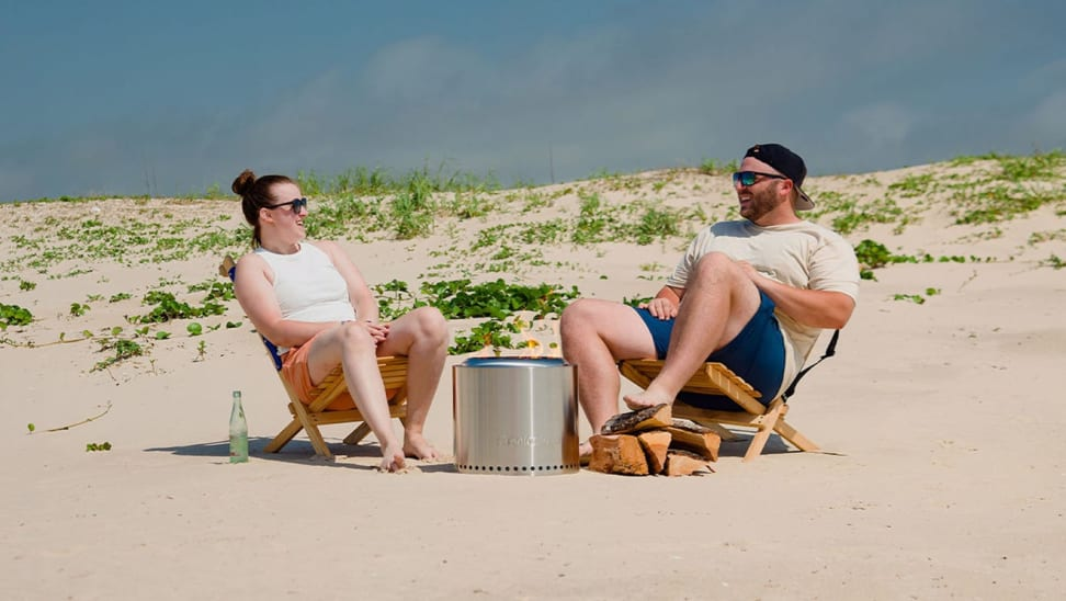 A couple sit around an outdoor fire pit on a beach.