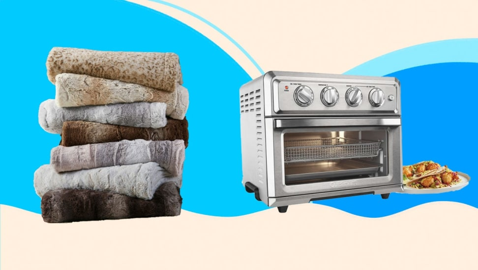 A stack of towels and a stainless steel toaster oven against a blue background.
