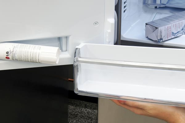 The LG LMXS30786S's water filter is hidden behind the lowest of the three left-hand side door shelves.