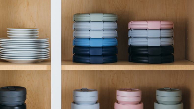 In a cabinet, stacks of Stojo bowls and cups are on display.