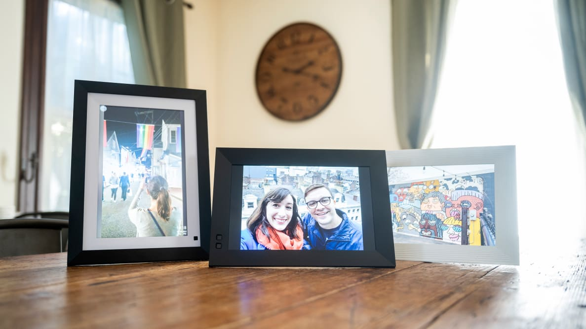 Three digital picture frames displaying family photos sit on a wooden table.