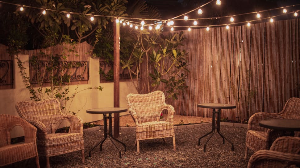 A backyard decorated with chairs and outdoor string lights.