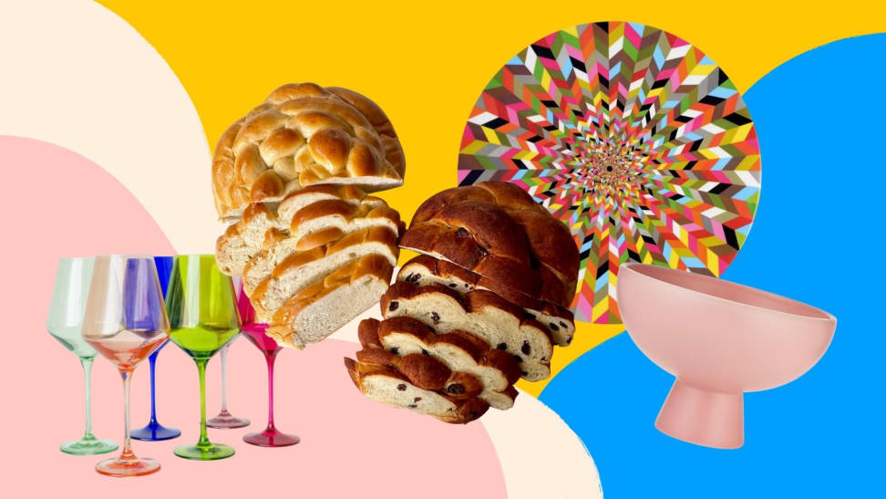 Colorful wine glasses, round challah loaves, a multicolored lazy susan, and a pink bowl arranged playfully on a colorful pink, yellow, and blue patterned background.