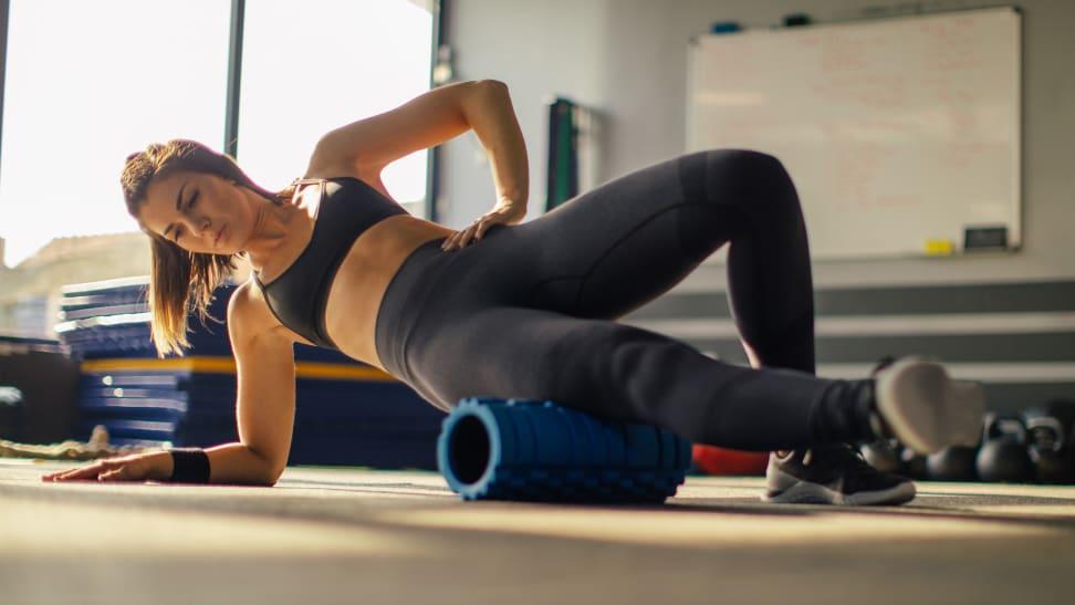 A woman foam rolling her hip.